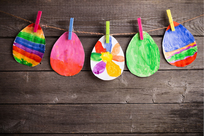 exemple d activité manuelle primaire, des oeufs en papier colorés à motif arc en ciel et fleur, suspendues par des pinces à linge à un fil pour fabriquer une guirlande de paques
