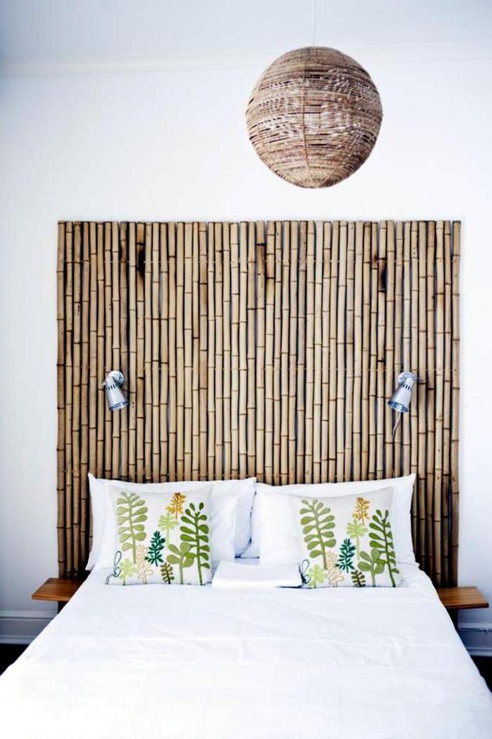 une chambre à coucher de style colonial avec tete de lit en bambou originale, une suspension en rotin et des motifs imprimés végétaux