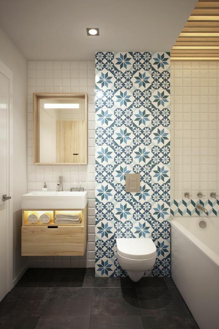 agencement salle de bain avec un mur en mosaïque bleue et blanche, carrelage du sol en marron, meuble suspendu en bois clair avec des étagères pour le rangement des serviettes, miroir rectangulaire au cadre en bois clair, meuble wc blanc suspendu, baignoire rectangulaire en blanc