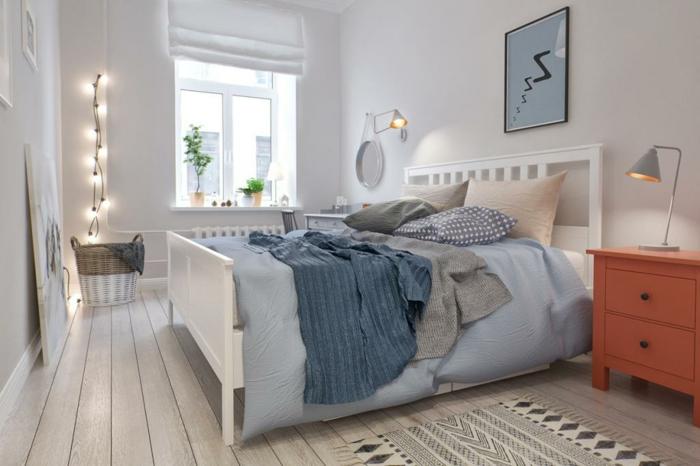 sol en planches de bois, guirlande lumineuse, peinture bleue encadrée, carpette beige; commoe en bois