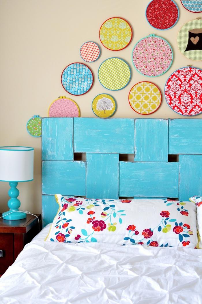 une chambre à coucher aux accents pop avec une tete de lit bois récup peinte en turquoise surmonté de cercles à broder détournés