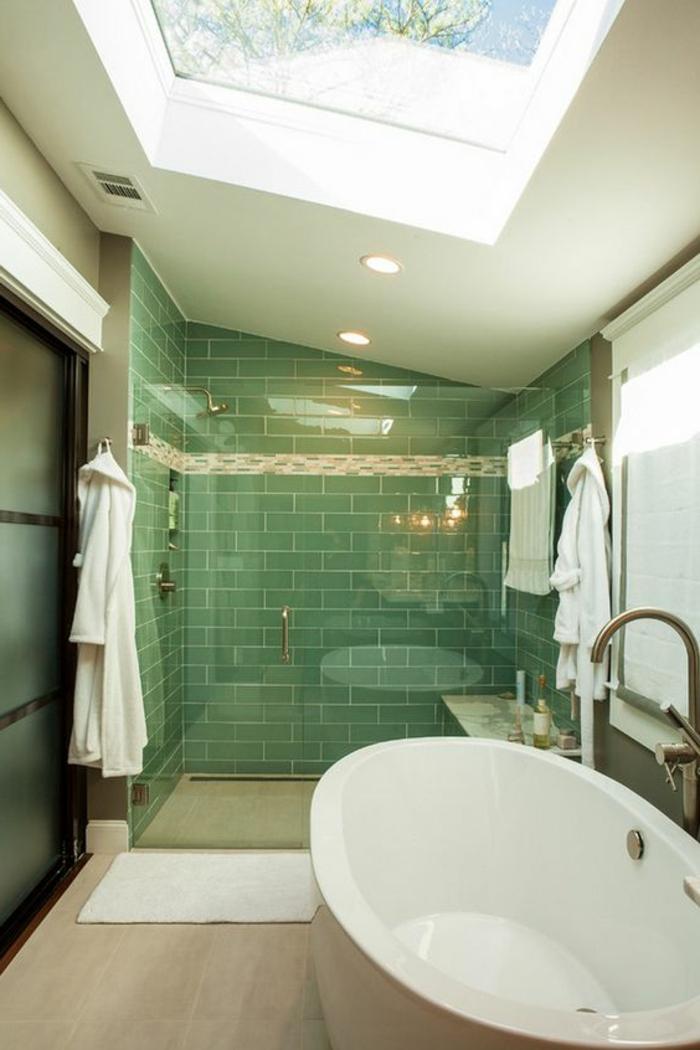 carrelage métro vert dans la cabine de douche, baignoire ovale, puits de lumière