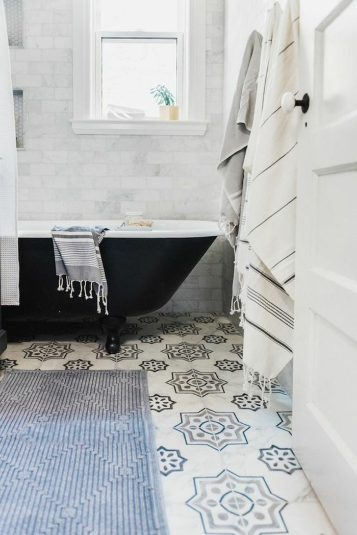 carrelage motifs vintage, étoiles, agencement salle de bain, baignoire noir et blanc, tapis rectangulaire en bleu pastel, porte blanche, fenêtre blanche rectangulaire