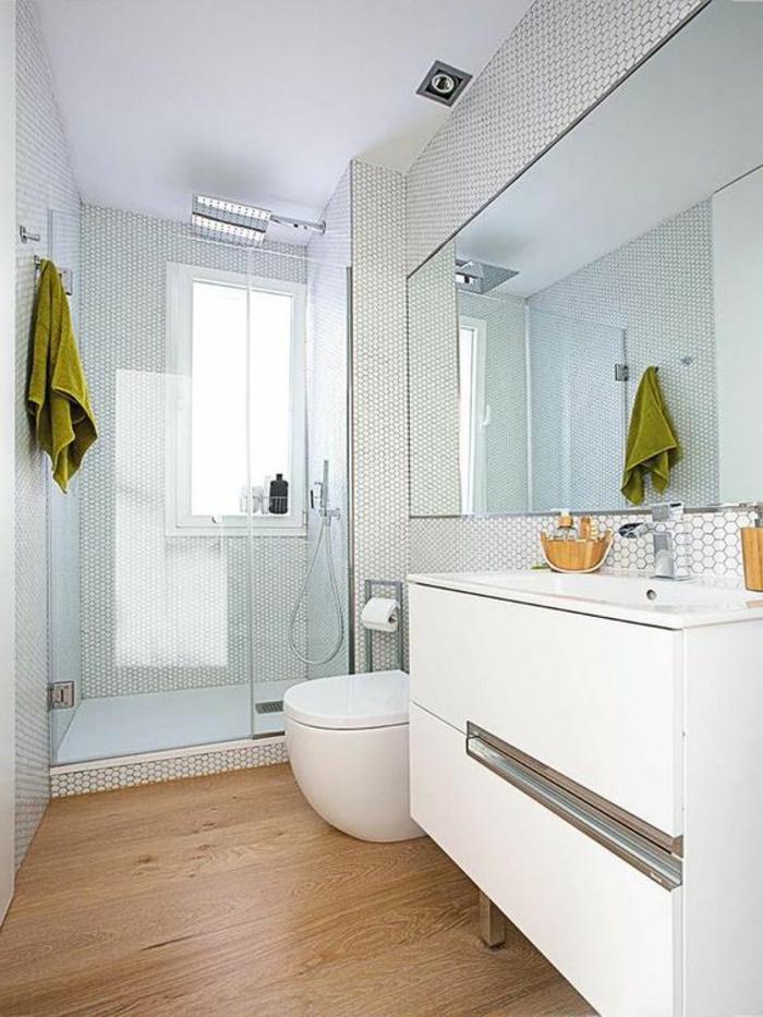 parquet PVC en beige aux nuances marron, salle de bain 6m2, meuble blanc avec des pieds en acier, carrelage mural en noir et blanc aux petits motifs graphiques, meuble wc au design ovale