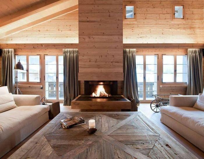 deux grands sofas beiges, sol en bois, cheminée, intérieur style chalet, fenêtres du plafond au sol