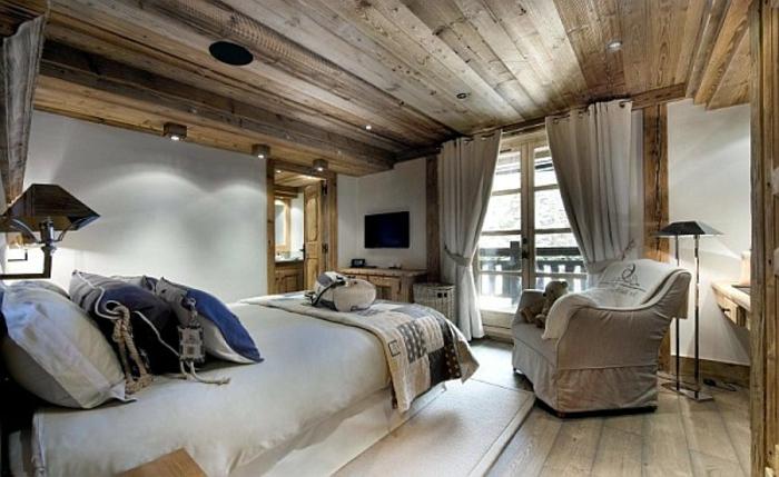 idée deco cocooning, intérieur de chalet rustique, fauteuil beige, murs peints blancs, plafond en bois