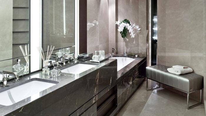 modèle de carrelage luxueux en beige et à design marbre noir, baignoire autonome en blanc et noir dans une salle de bain aménagée en longueur