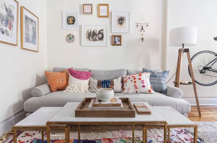 canapé nuance gris, tapis coloré, tables basses, mur décoré de cadres de tailles diverses, parquet clair