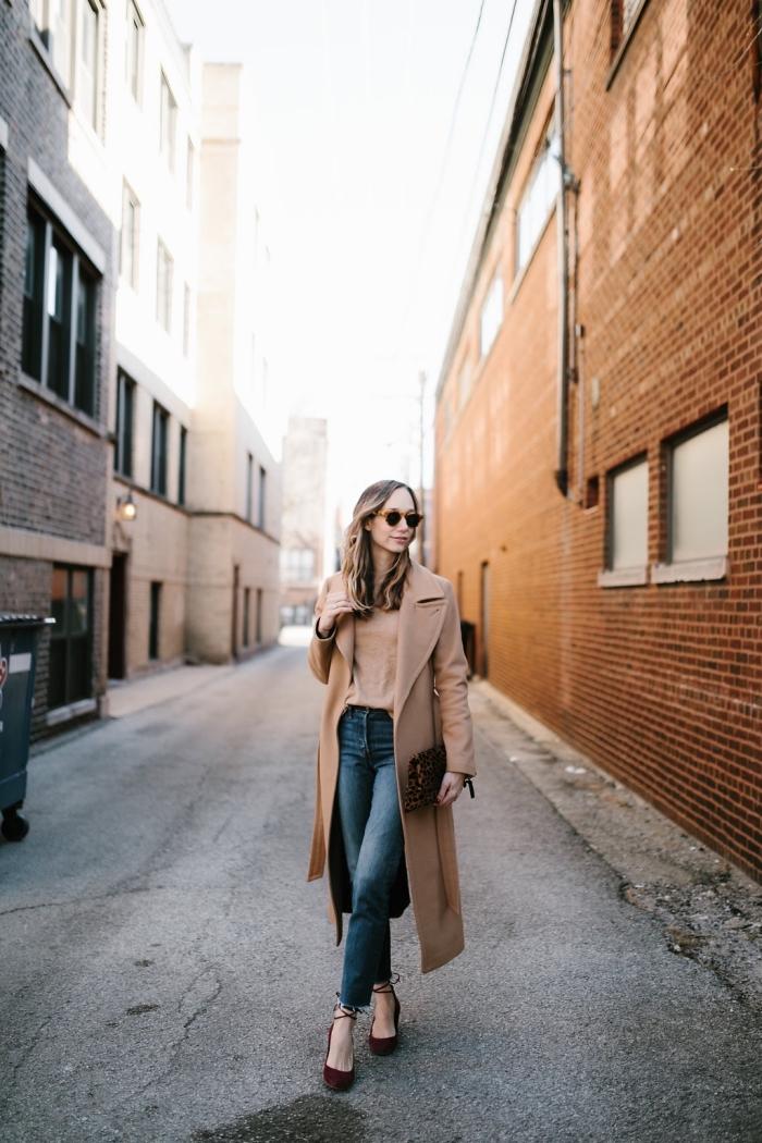 modèle de jeans à taille haute combiné avec blouse beige et manteau ultra long femme avec chaussures et sac à main bordeaux