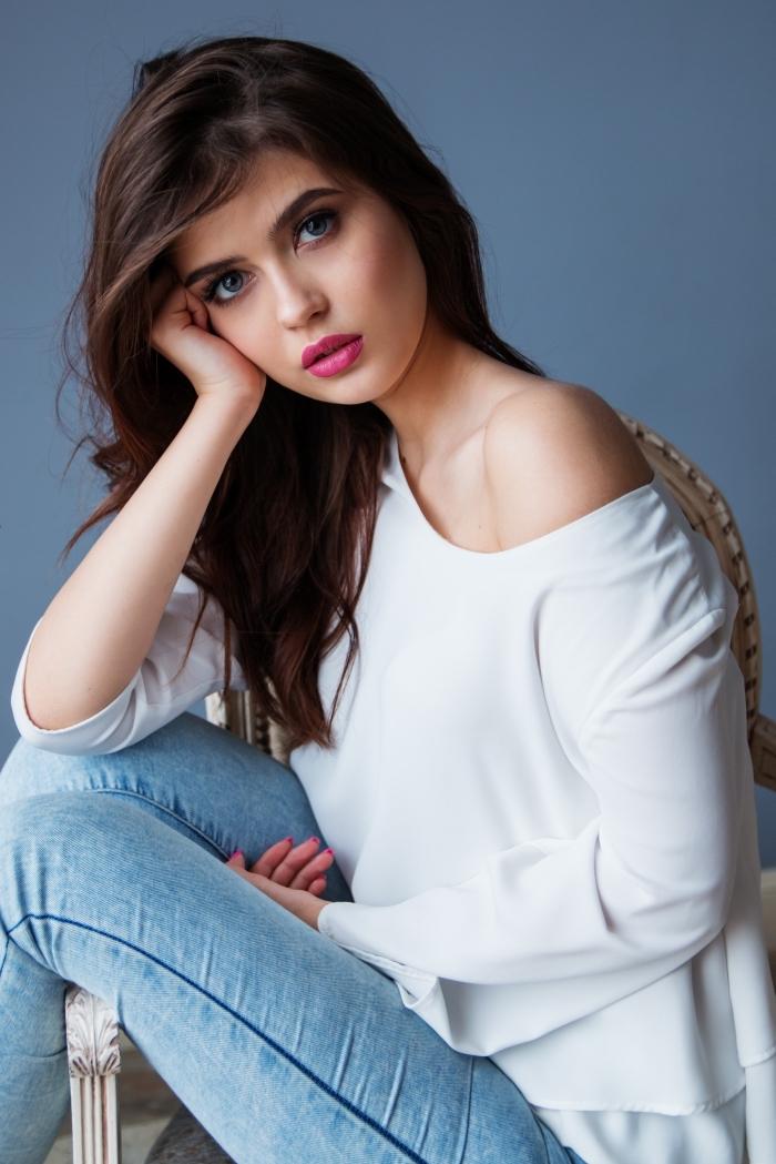 jeune fille habillée en style casual chic avec paire de jeans clair et blouse blanche à design col asymetrique, couleur cheveux chocolat longs et naturellement bouclés