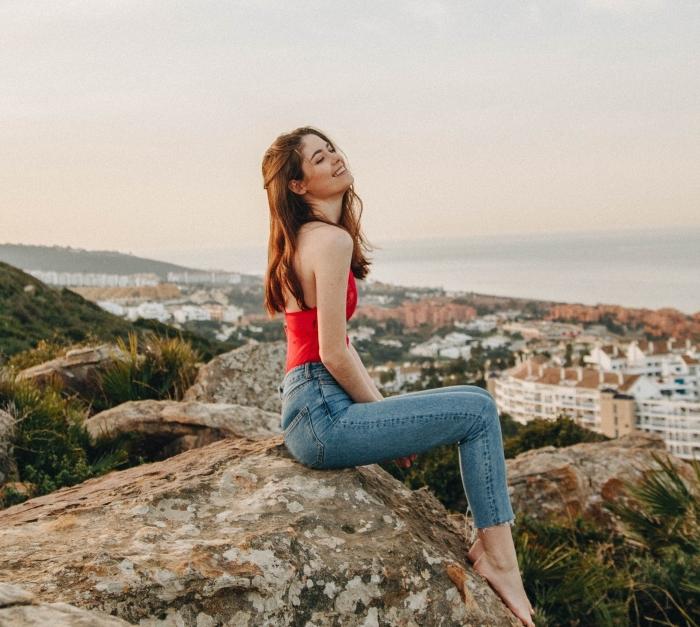 coloration cheveux longs cuivrés, tenue en style casual avec jeans clairs et top crop femme rouge, promenade dans la nature