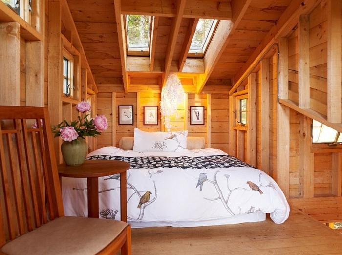 intérieur style cottage, lit sous les toits, banquette en bois et textile, vase avec des fleurs, lit sous la fenêtre