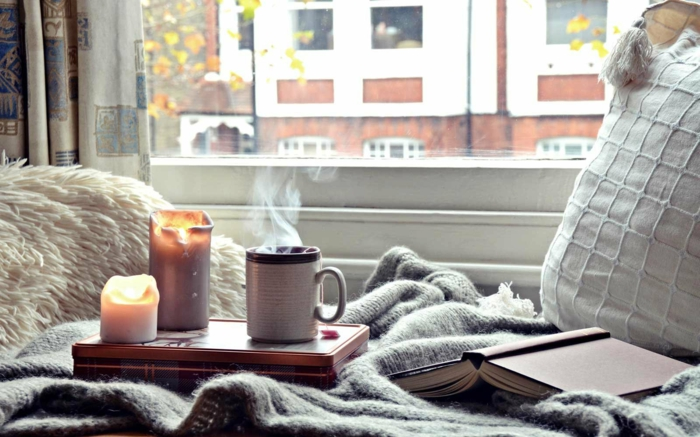 coin de repos cosy et beau, bougies allumées, plaid gris, coussin gris près de la fenêtre, déco chambre cocooning