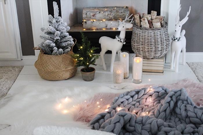 déco de Noel miraculeuse, plaid tricoté, bougies allumées, panier tressé avec petit sapin, bûches décoratives