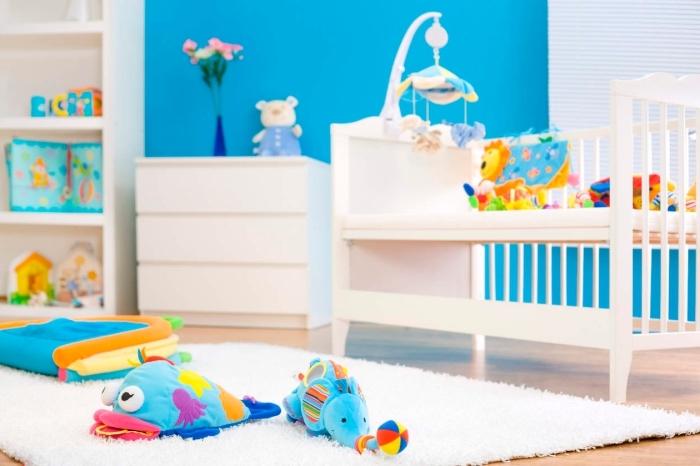 comment décorer la chambre bébé fille ou garçon en blanc et bleu, meubles de bois blanc sur un parquet de bois clair avec tapis moelleux