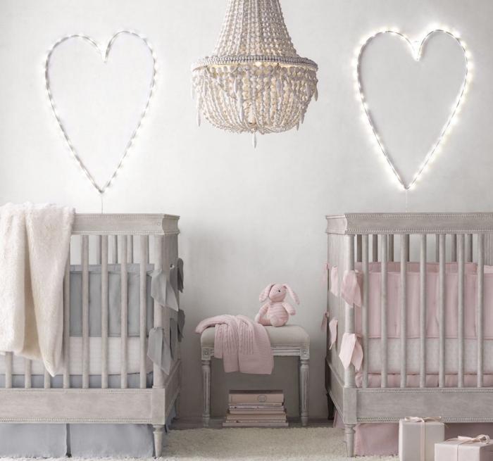 chambre bébé fille ou garçon aux murs blancs avec décoration lumineuse et deux lit à barreaux de bois gris avec linge gris et rose pastel