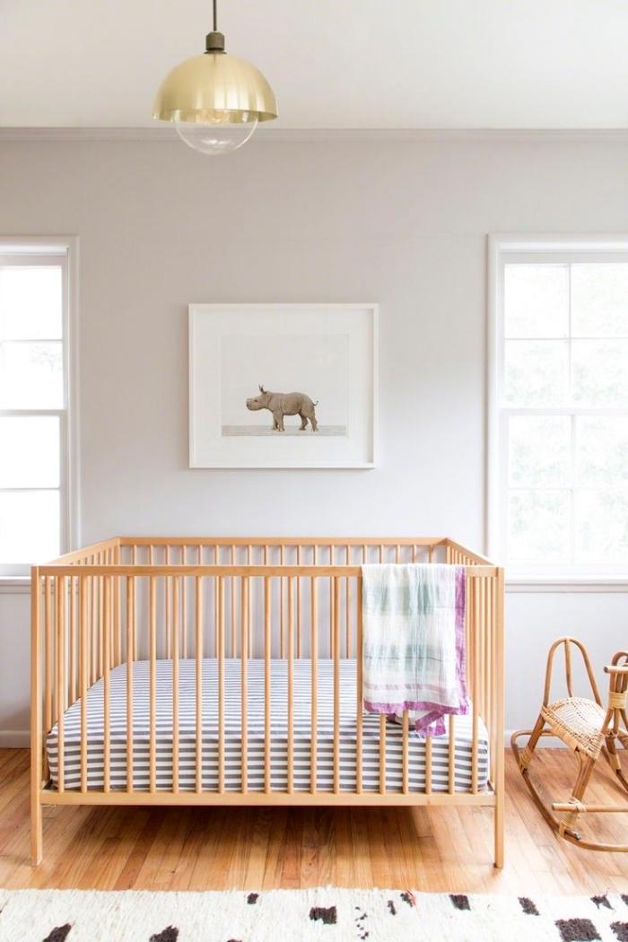 modèle de grand lit bebe fille ou garçon dans une chambre beige au plancher de bois clair avec tapis blanc et marron