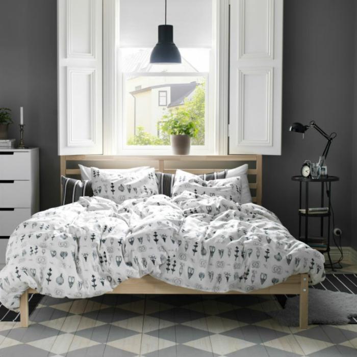 sol à patterns géométriques, linge de lit avec des motifs nordiques, lampe noire, fenêtre à volets blancs