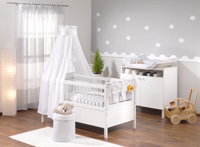 modèle de chambre bebe complete aux murs gris et blanc avec plancher de bois foncé et un lit à barreaux avec baldaquin blanc