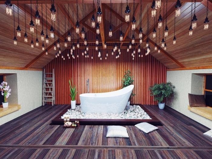 aménagement sous comble avec une salle de bain à plafond et plancher de bois, modèle de baignoire autonome blanche