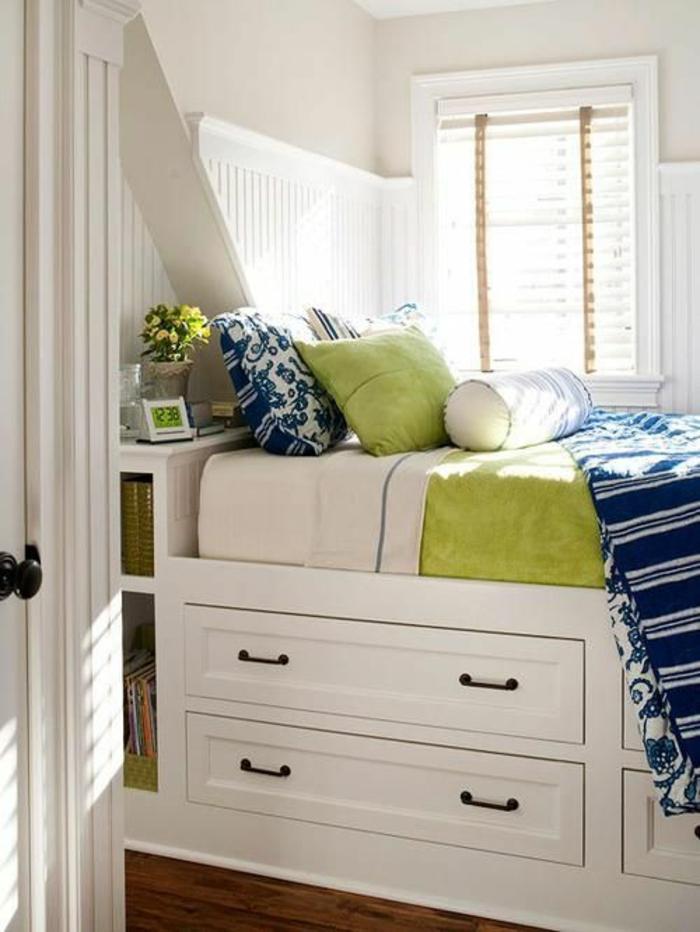déco chambre étudiant, micro chambre avec lit et des grands tiroirs type caissons avec des poignées noires, decoration interieur appartement, espace orné de coussins carrés et ronds, couverture de lit en couleur réséda, sol avec parquet en nuances marrons