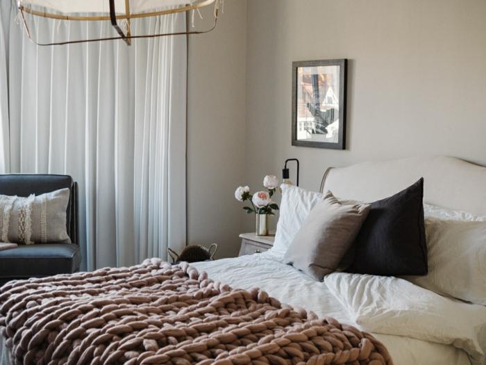 jeté de lit rose, coussins simples, rideaux blancs, fauteuil avec coussin, chevet et bouquet de pivoines
