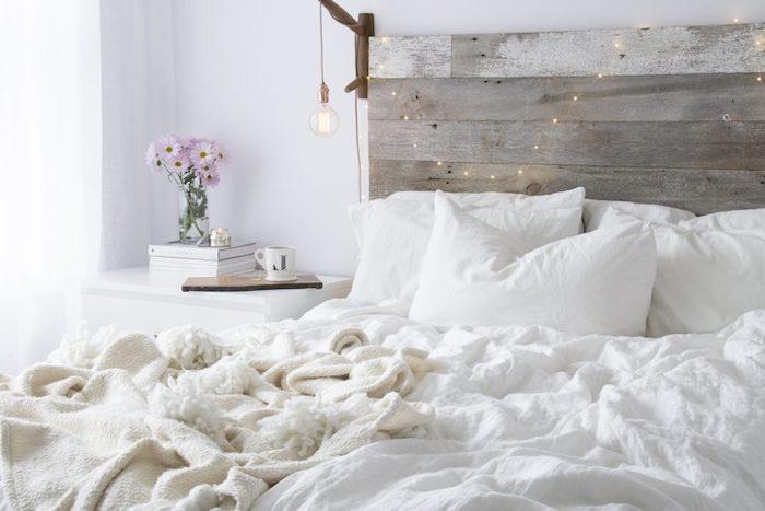 exemple pour fabriquer une tete de lit en bois avec suspension ampoule et guirlande de noel, linge de lit blanc