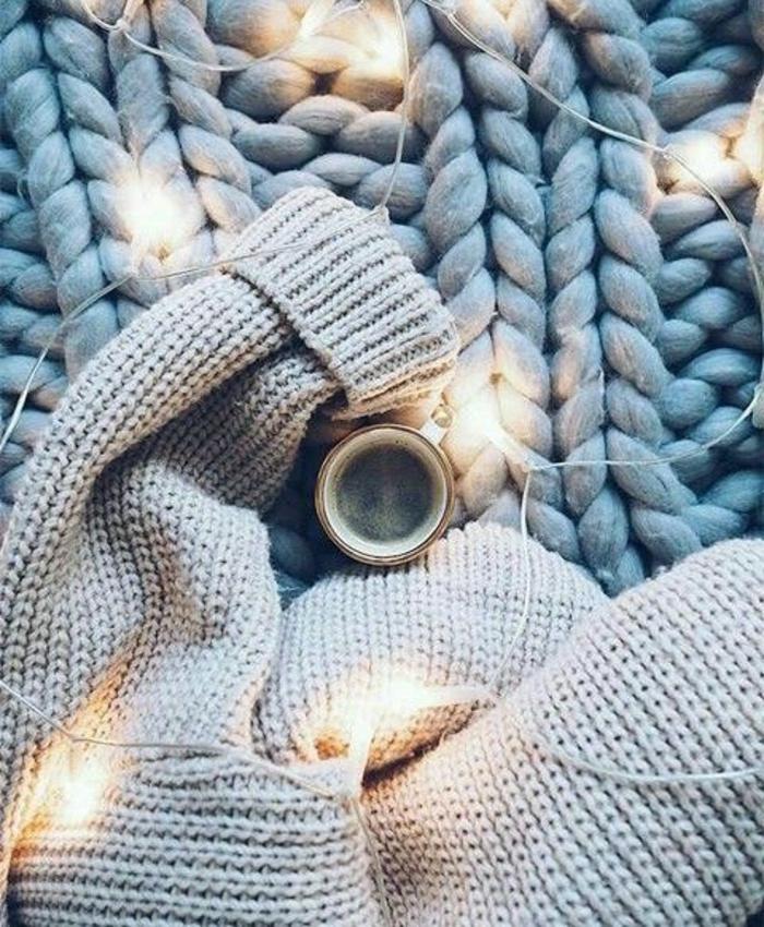 plaid gris, tasse de café chaud, pull gris cosy et moelleux, ambiance cocooning à la maison