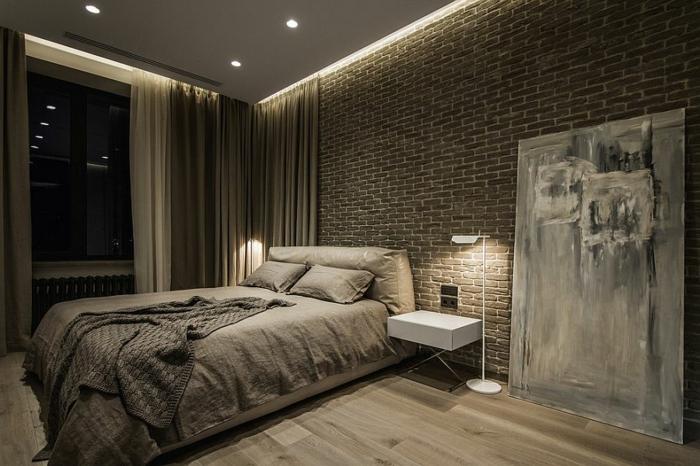mur en briques, lit beige, petit chevet blanc, lampe de sol moderne, amenagement chambre minimaliste