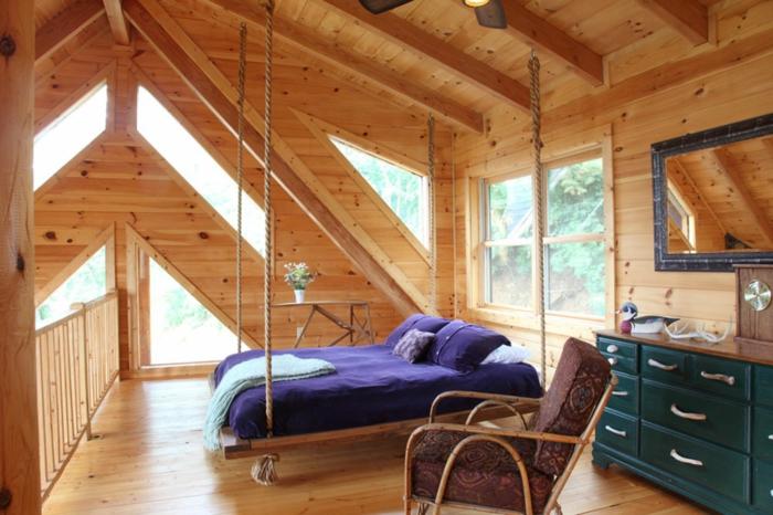 lit suspendu dans une chambre style attique, placard bleu, fauteuil marron