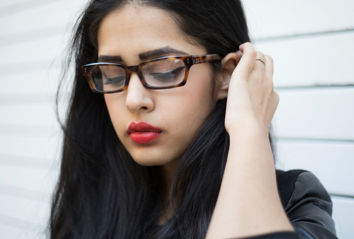 lunette visage rond, jeune femme avec monture épaisse en noir et marron, sourcils épais, rouge a lèvres en rouge, cheveux longs en noir