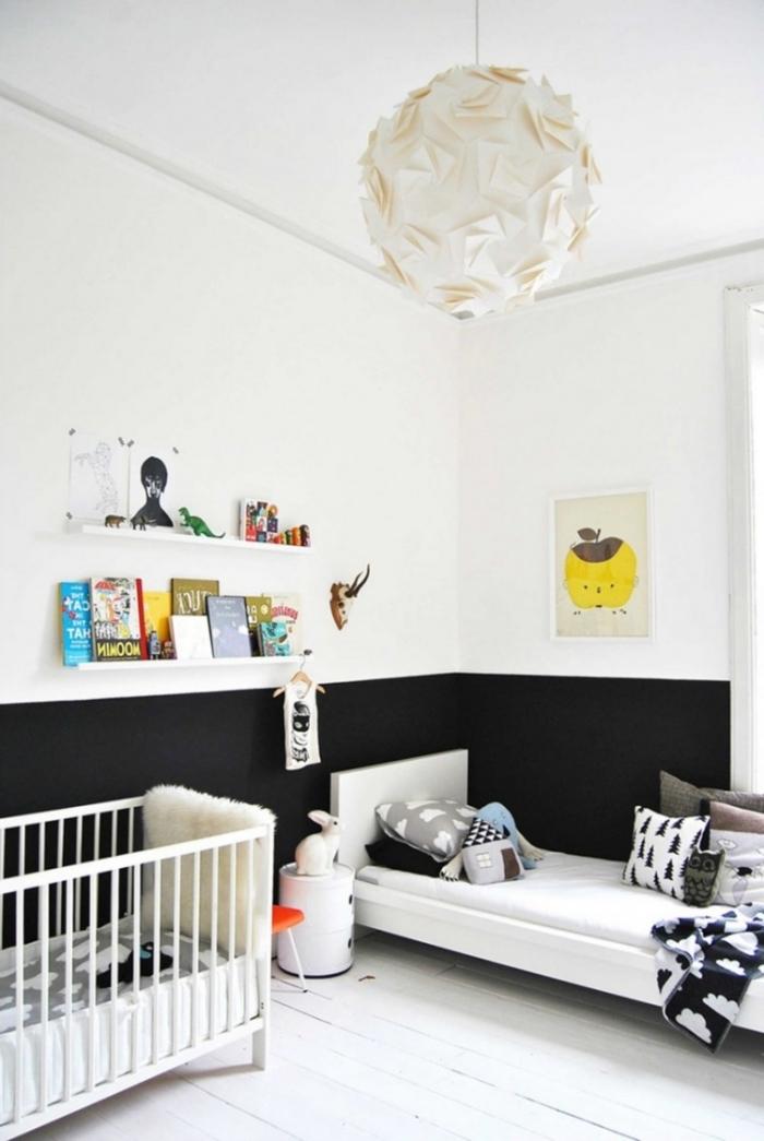murs blanc et noir dans la chambre bébé fille avec lit blanc couvert de coussins décoratifs à imprimés scandinave