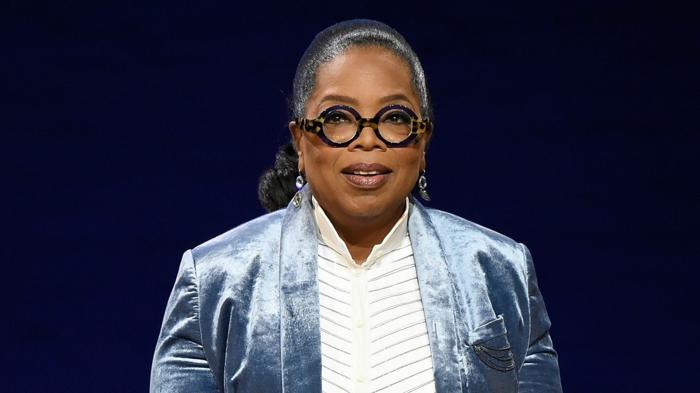 Oprah Winfrey avec une monture lunette en noir avec des imprimés animaliers, comment choisir ses lunettes pour un visage ovale