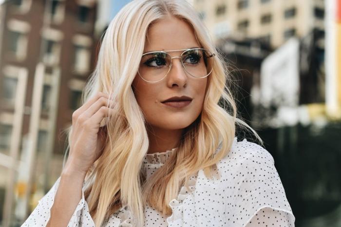 monture lunette ultra fine, femme aux cheveux longs blonds, blouse blanche avec des petits pois noirs, paysage urbain