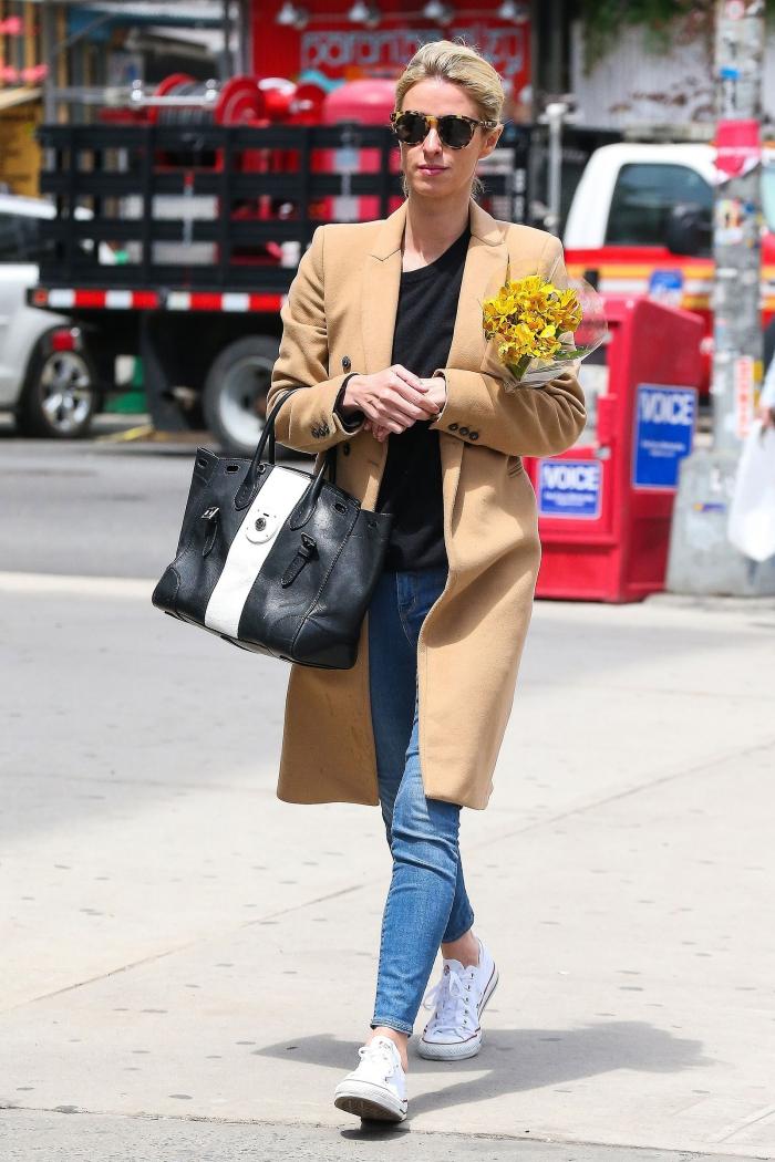 modèle de sac à main en cuir blanc et noir, look casual chic en jeans clairs et baskets blancs, coiffure cheveux blonds attachés en chignon bas