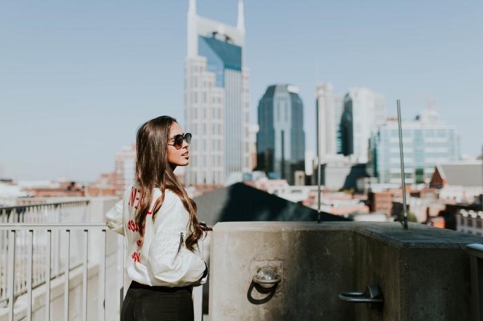 balayage miel léger avec pointes cuivrées sur cheveux de base châtain foncé, look urban avec jeans foncés et bomber blanc femme