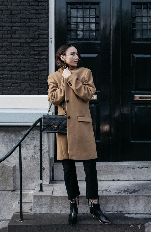 femme chic et stylée en manteau long oversize beige et pantalon noir avec bottines et sac à main de cuir noir