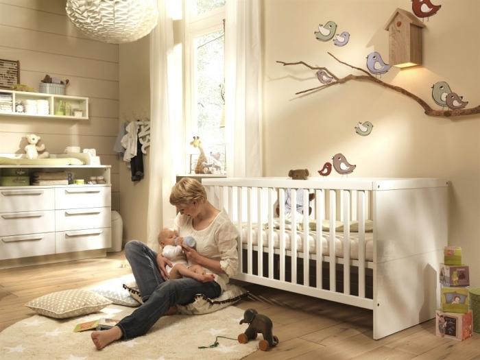 modèle de la chambre bébé garçon aux murs beige et plafond de bois couvert de tapis et coussins beige