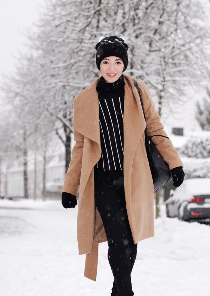comment bien s habiller en noir et beige avec pantalon slim noir et pull over loose rayé en blanc et noir, accessoires gants et bonnet noirs
