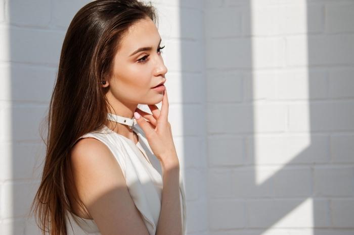 robe blanche avec chocker en cuir blanc, femme aux cheveux super longs de couleur châtain foncé aux reflets dorés