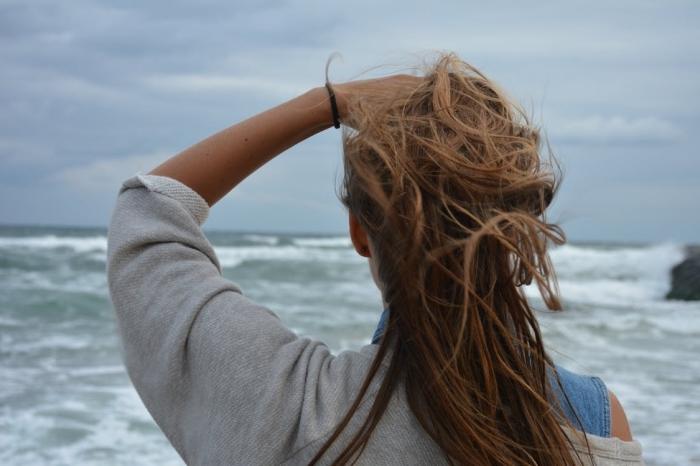 modèle de coloration balayage sur cheveux chatain aux reflets caramel, tenue en gilet gris et robe denim pour une promenade au bord de la mer