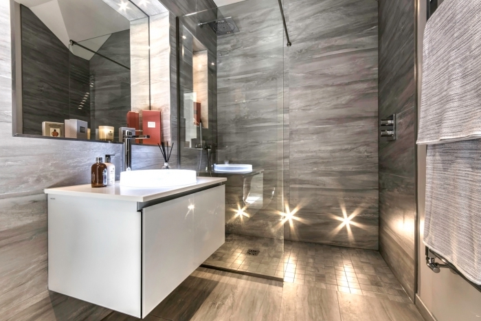 modèle de cabine de douche avec paroi de verre et carrelage gris, déco de petite salle de bain en gris avec armoire blanche