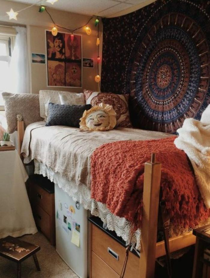 aménagement chambre 10m2 en style hyppie, ameublement boho chic, mur recouvert de tissu aux motifs de mandala, petit frigo blanc sous le lit, guirlande d'ampoules lumineuses multicolores suspendue au plafond