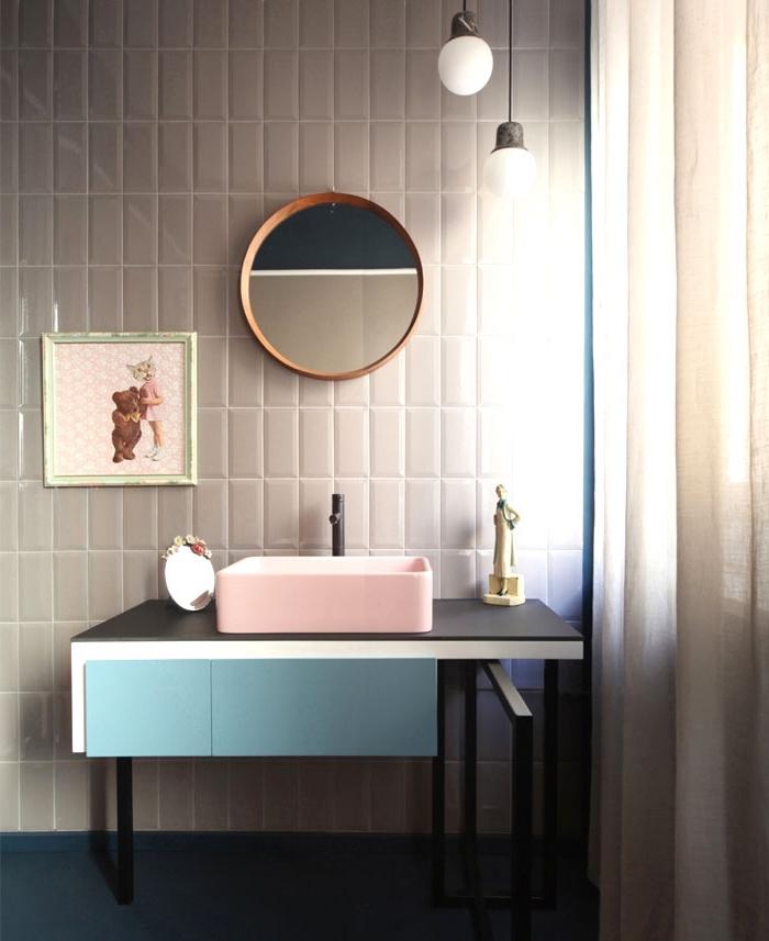 comment intégrer les couleurs pastel dans la salle de bain moderne avec miroir rond de bois et armoires en rose noir et bleu