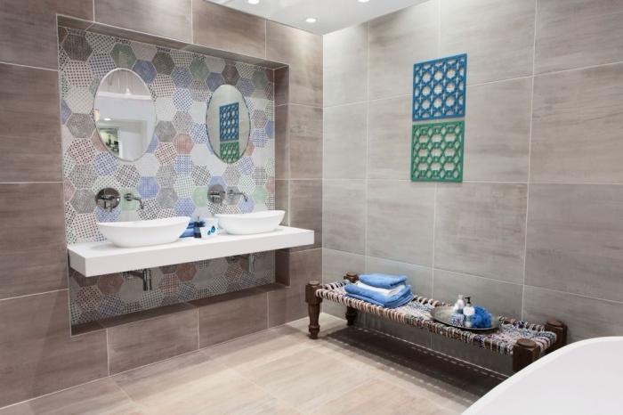 modele salle de bain au carrelage beige avec coin lavabo à design couleurs pastel et miroir oval, baignoire autonome blanche