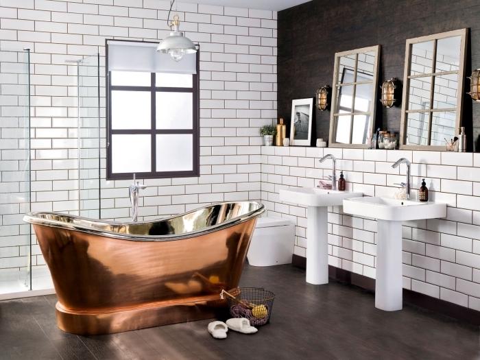 esprit campagnard et moderne avec revêtement mural en carrelage à imitation briques blanches et baignoire cuivrée, double vasque salle de bain blanche