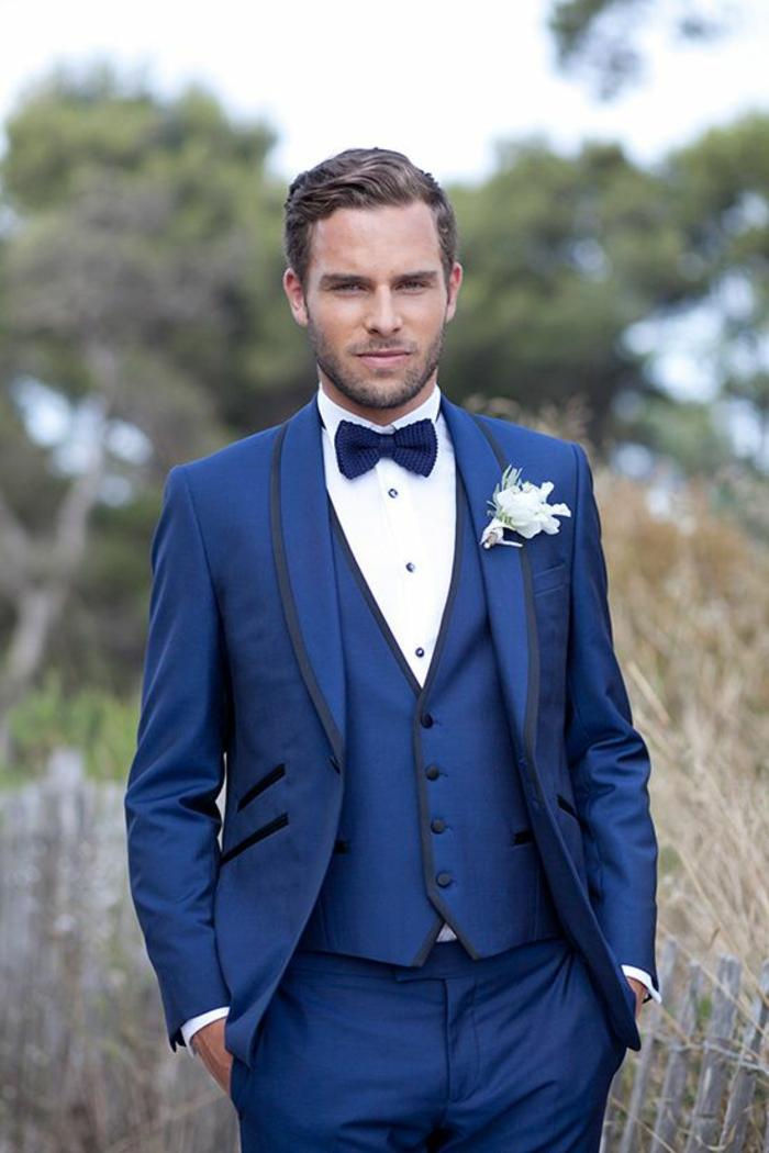 costume 3 pièces homme, gilet avec des petits boutons noirs, nœud papillon en bleu roi, revers de la veste en satin noir, poches mises en valeur avec du satin noir