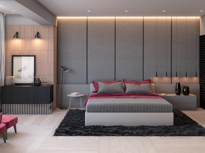 tapis couleur gris anthracite, linge de lit rouge et gris, parquet clair, mur gris et suspensions originales
