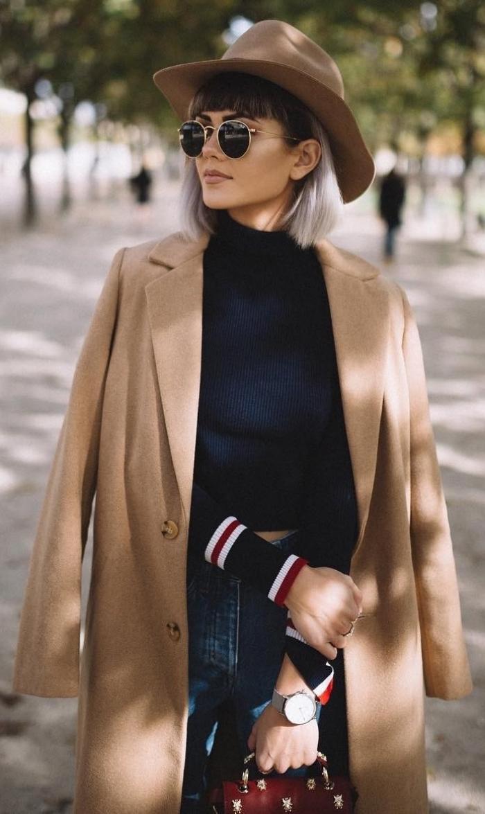 vision élégante et chic avec paire de lunettes rondes noir et or combinées avec une capeline beige, tenue casual chic en jeans et blouse bleu foncé