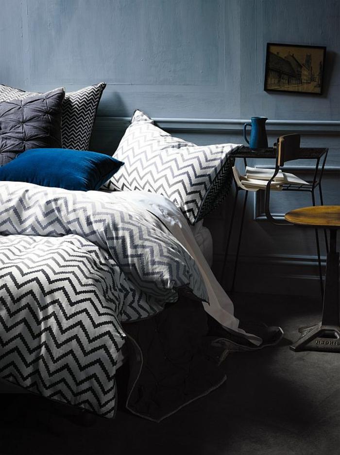 coussin bleu, linge de lit à zigzags, mur couleur colombe, petite table haute, chaise en bois et fer industrielle